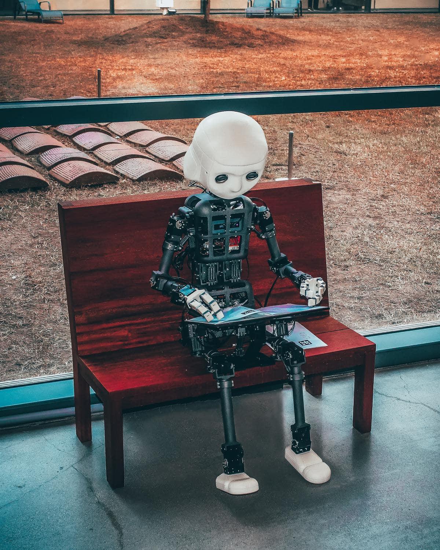 Fake News. Ein Bot sitzt auf einer Bank und liest eine Zeitung