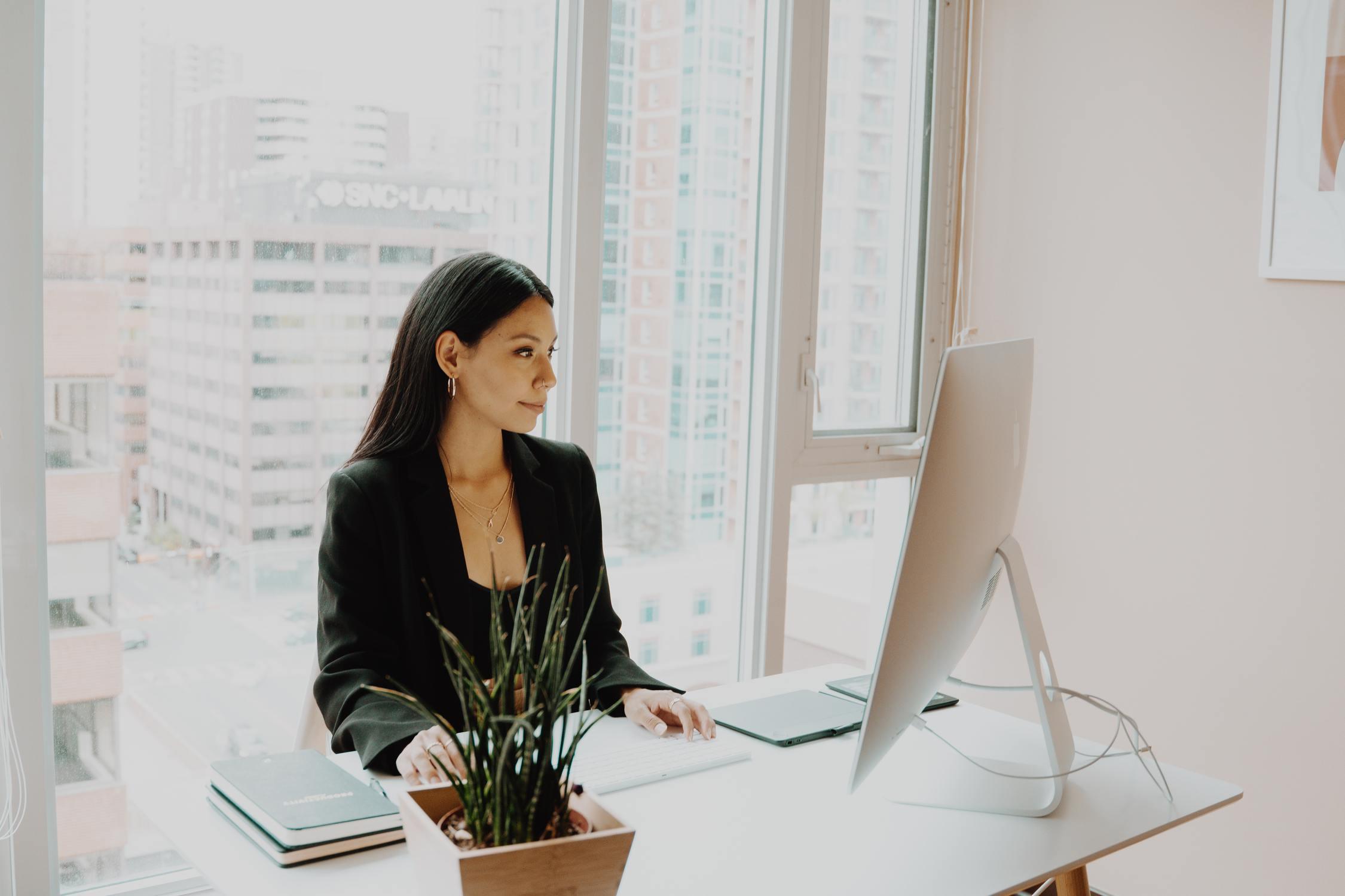 Junge Frau sitzt vor Computer und lächelt