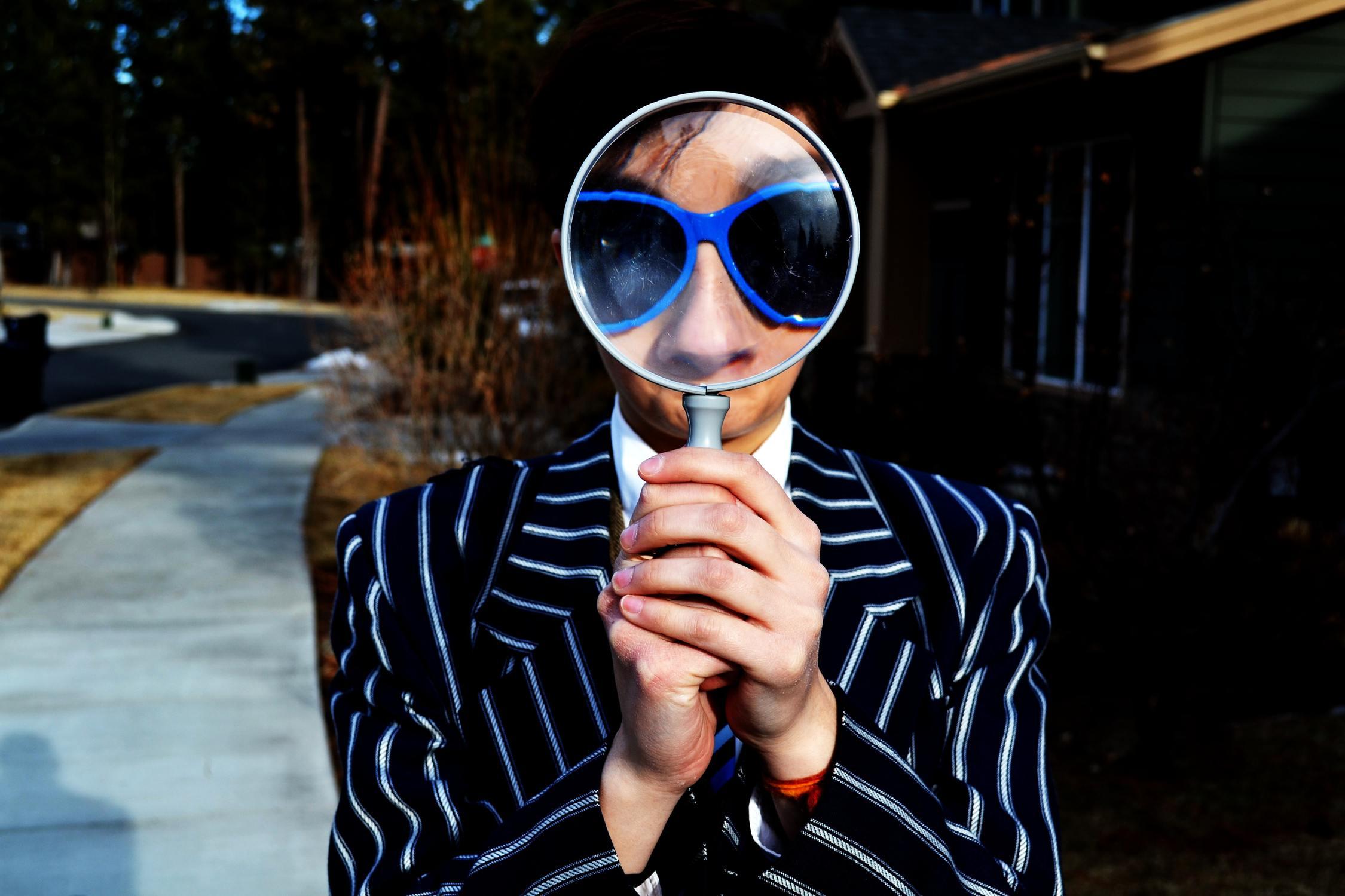 Mensch mit Sonnenbrille schaut durch Lupe