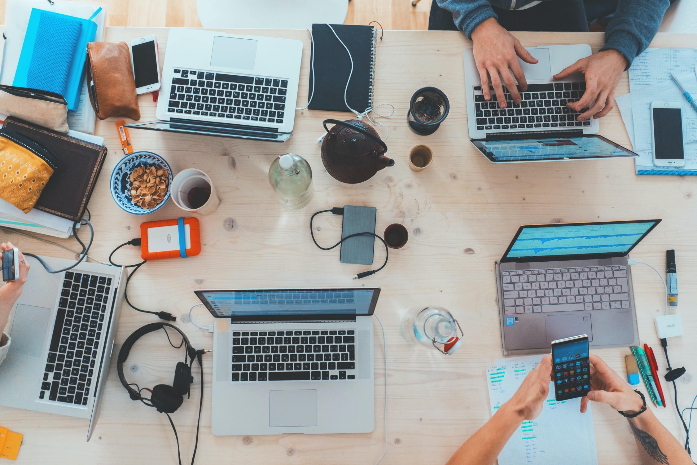 Gemeinsames Arbeiten an einem Tisch mit Laptops