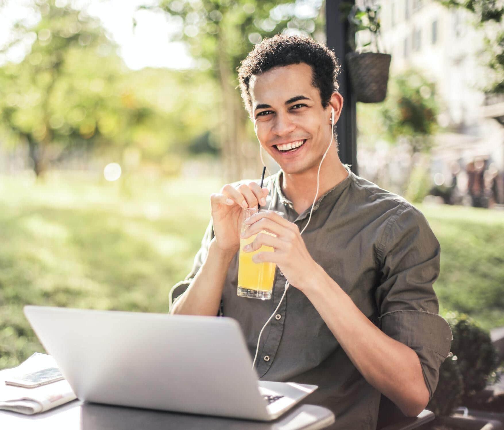 Junger Student sitzt im Freien und lächelt, weil ihm sein Technik-Studium Spaß macht