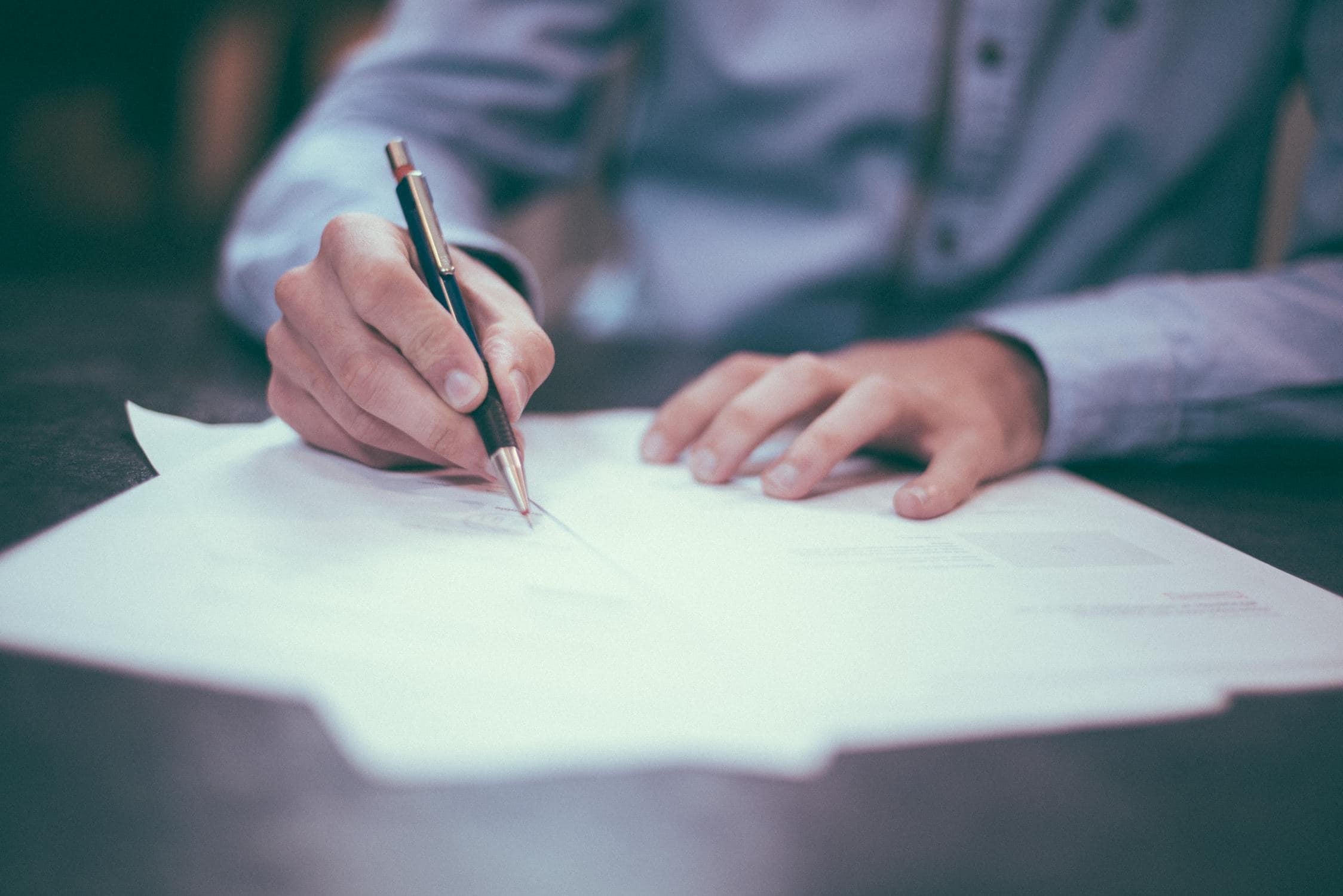 Hände, die einen Stift in der Hand halten und auf Papier schreiben
