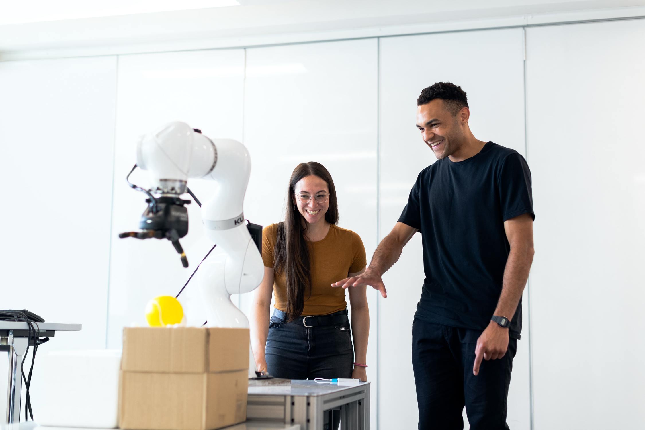 Junge Frau und junger Mann bedienen lachend gemeinsam einen Roboter in einer HTL
