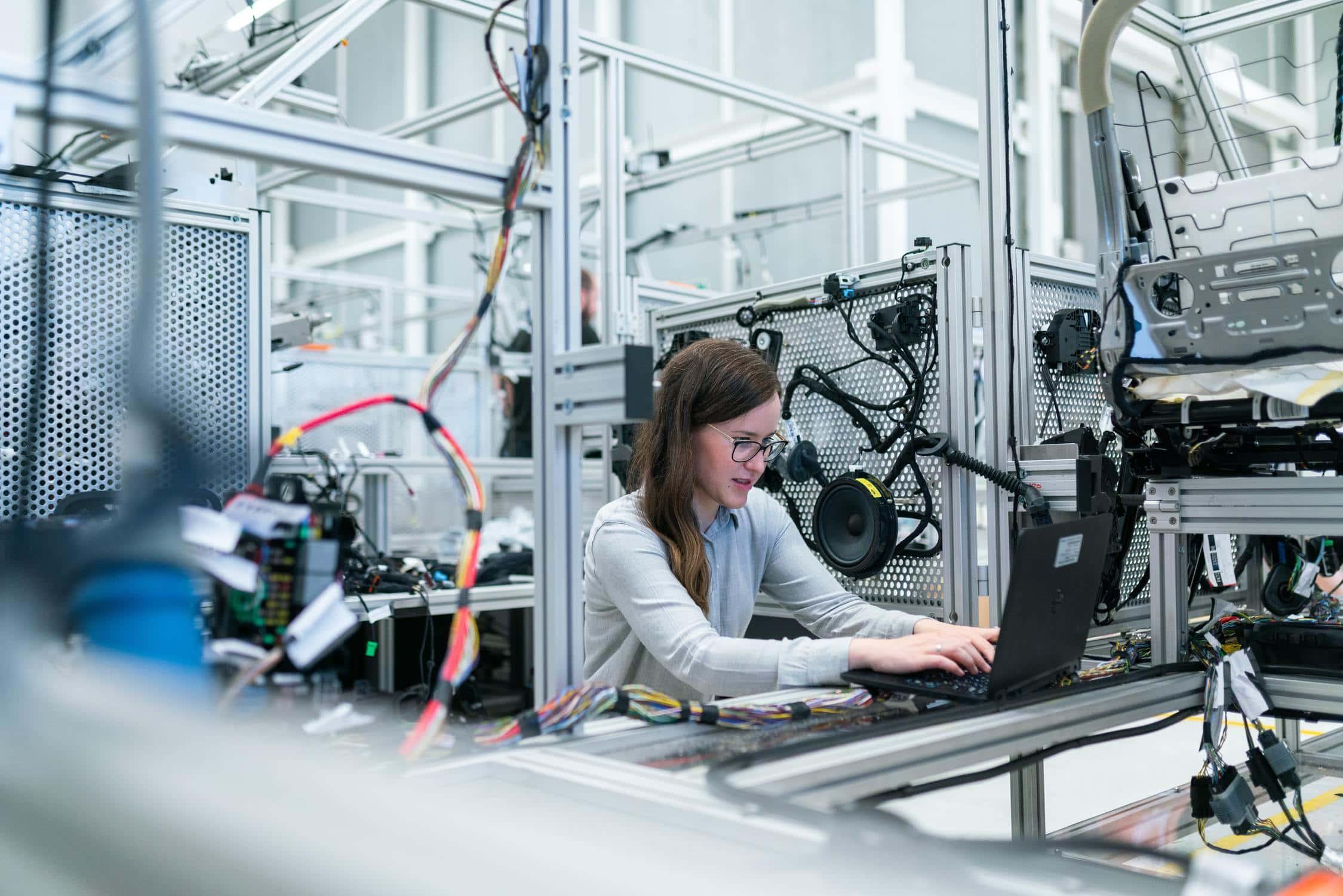 Junge Frau sitzt in großem Technik-Labor vor Computer und arbeitet an ihrer Forschung
