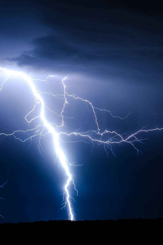 Blitz schlägt bei Gewitter auf dunkler Fläche ein