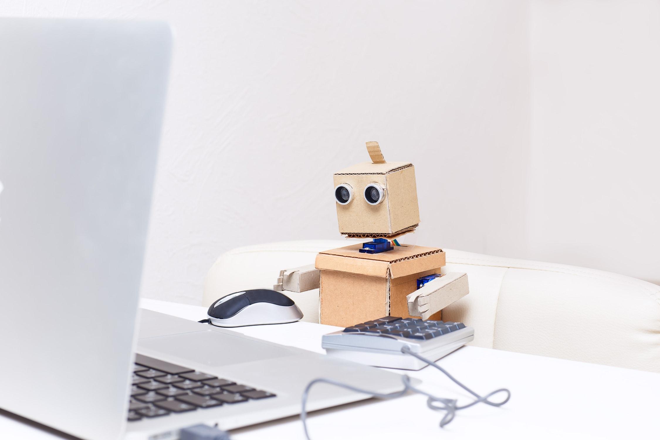 Was macht man als Machine Learning Engineer? Symbolbild mit Roboter vor Laptop