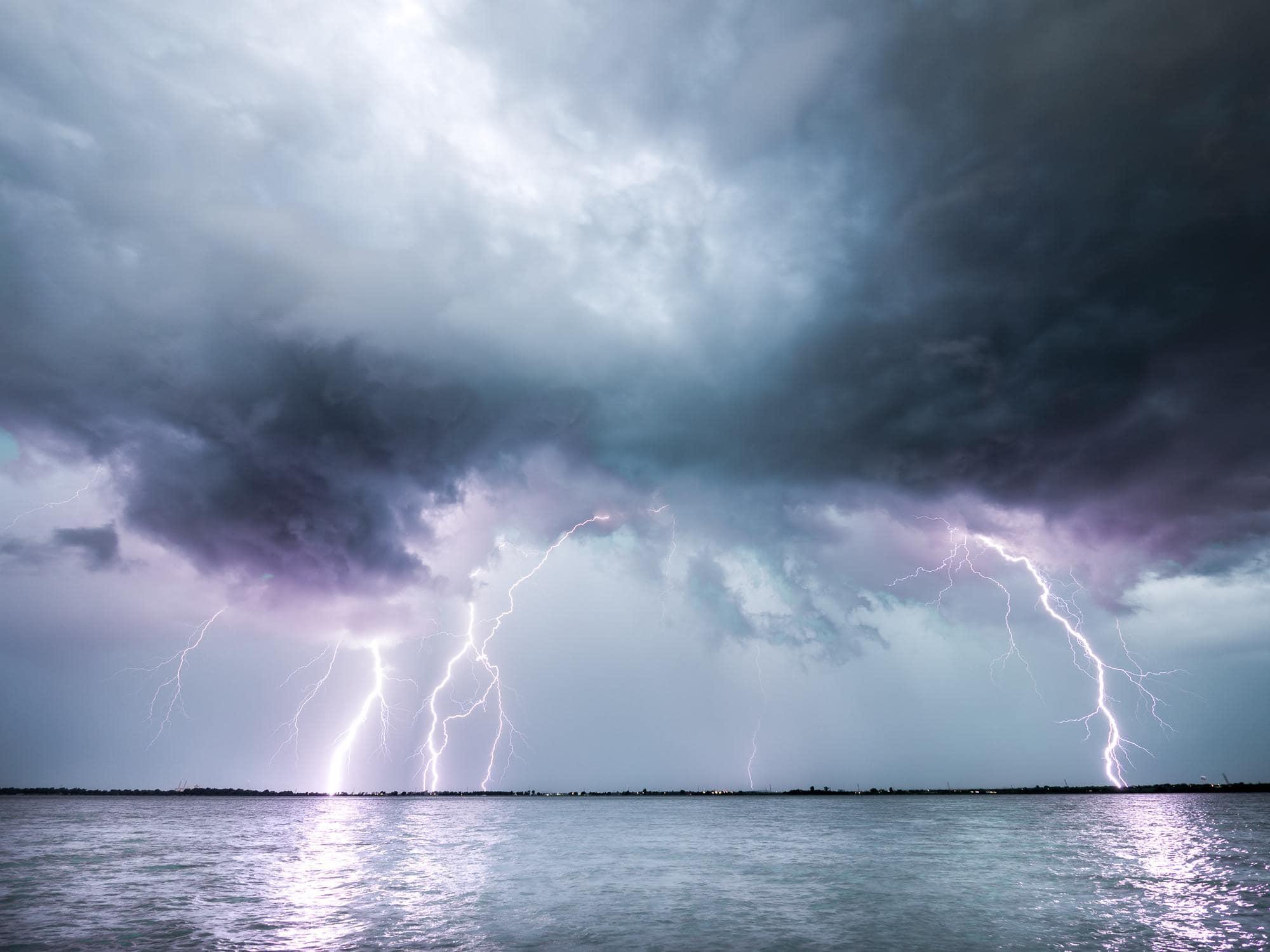 Gewitter über Wasser mit einschlagenden Blitzen