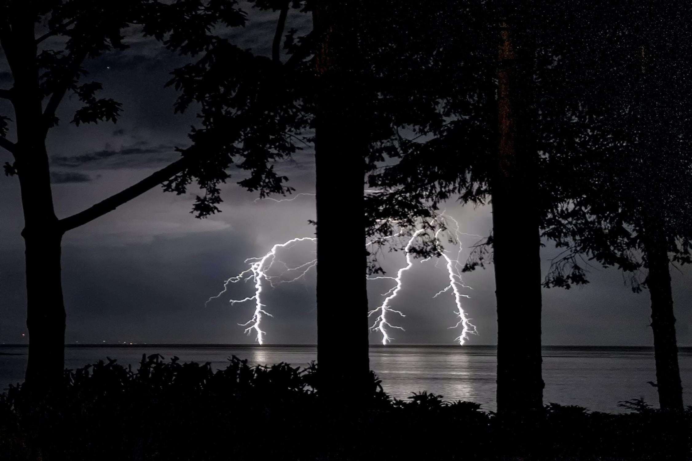Ein Gewitter am See wird vom Wald aus beobachtet